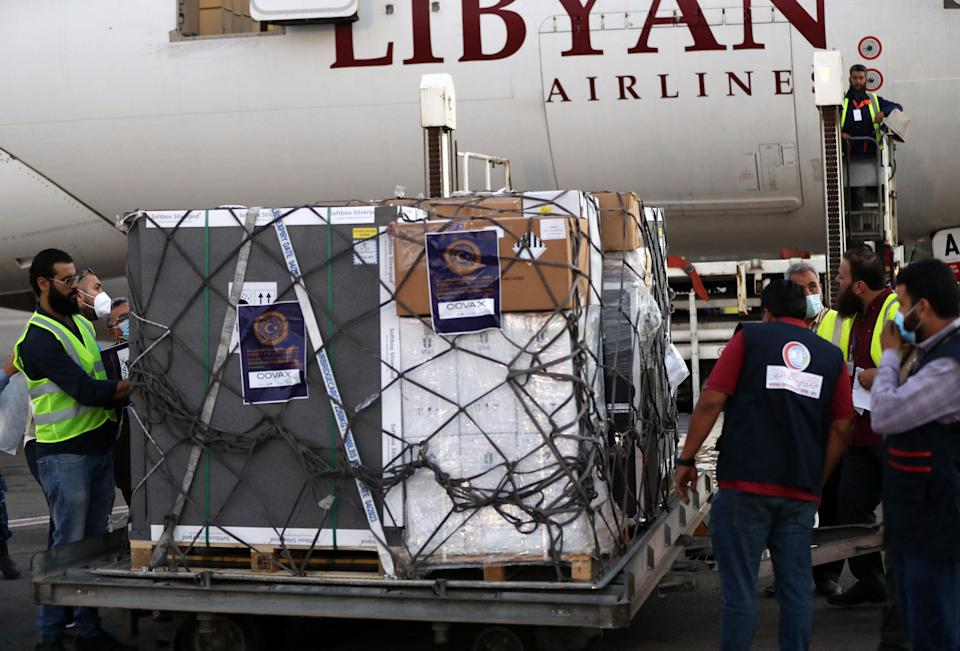 Employees unload from a plane a shipment of Astra Zeneca vaccine doses against the coronavirus upon its arrival at the airport of the Libyan capital Tripoli, on May 19, 2021. (Photo by Mahmud TURKIA / AFP) (Photo by MAHMUD TURKIA/AFP via Getty Images)