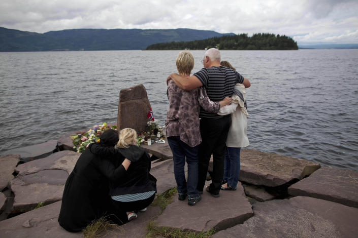 FILE - In this Monday, July 25, 2011 file photo, relatives of a victim gather to observe a minute's silence on a campsite jetty on the Norwegian mainland, across the water from Utoya island, seen in the background, where people have been placing floral tributes in memory of those killed in the shooting massacre on the island. At 3.25 p.m. on July 22, 2021, a ray of sun should have illuminated the first of 77 bronze columns on a lick of land opposite Utoya island outside Oslo. Over the next 3 hours and 8 minutes, it would have brushed each column in turn, commemorating every person killed by right-wing terrorist Anders Breivik. But on the ten-year anniversary of the terror, the memorial remains a construction site. (AP Photo/Matt Dunham, File)
