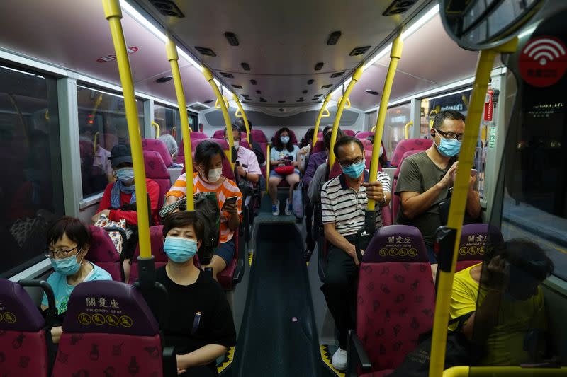 People wearing face masks sit on a bus in Hong Kong