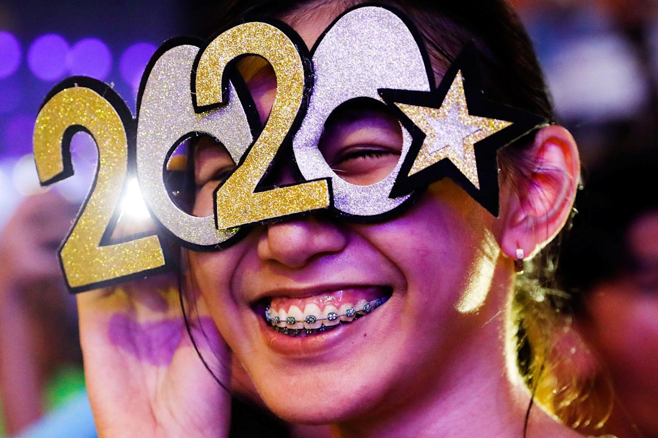 A reveller wears glasses shaped like the year 2020 during the New Year's Eve party in Quezon City, Metro Manila, Philippines December 31, 2019. REUTERS/Eloisa Lopez