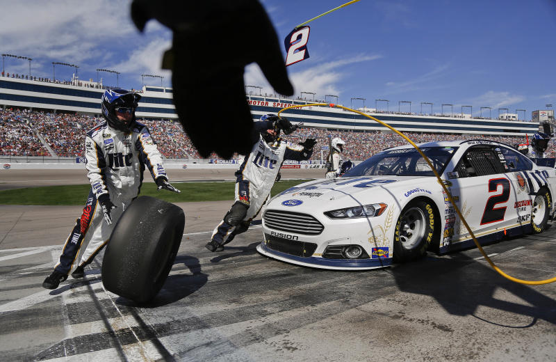 A pit crew member reaches to grab one of the used tires off of Brad Keselowski's car during a pit stop at a NASCAR Sprint Cup Series auto race on Sunday, March 9, 2014, in Las Vegas. (AP Photo/Julie Jacobson)