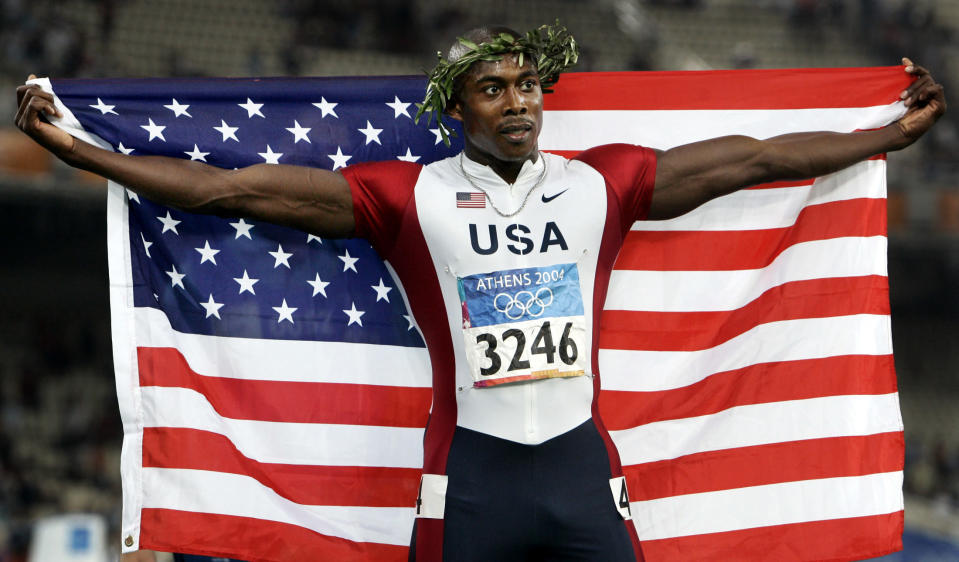 FILE - Shawn Crawford celebrates after winning the 200-meter finals at the 2004 Olympic Games in Athens, in this Thursday Aug. 26, 2004, file photo. Crawford ran track and Clemson University. Clemson track is one of the 85 Division I sports programs to be shuttered in recent years, a trend that picked up steam because of financial strains exposed during the COVID-19 pandemic. Olympic and college-sports leaders fear it will only continue as changes in the college system take hold. (AP Photo/Anja Niedringhaus, File)