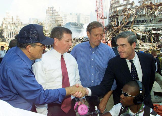 <p>FBI Director Robert Mueller (R) shakes hands with New York Mayor Rudolph Giuliani (L) at the World Trade Disaster site in New York 21 September 2001. Attorney General John Ashcroft (2nd L), accompanied by Mueller and New York Governor George Pataki (2nd R), got a firsthand look at the World Trade Center devastation and promised to rebuild New York. (Photo: Mike Segar/AFP/Getty Images) </p>