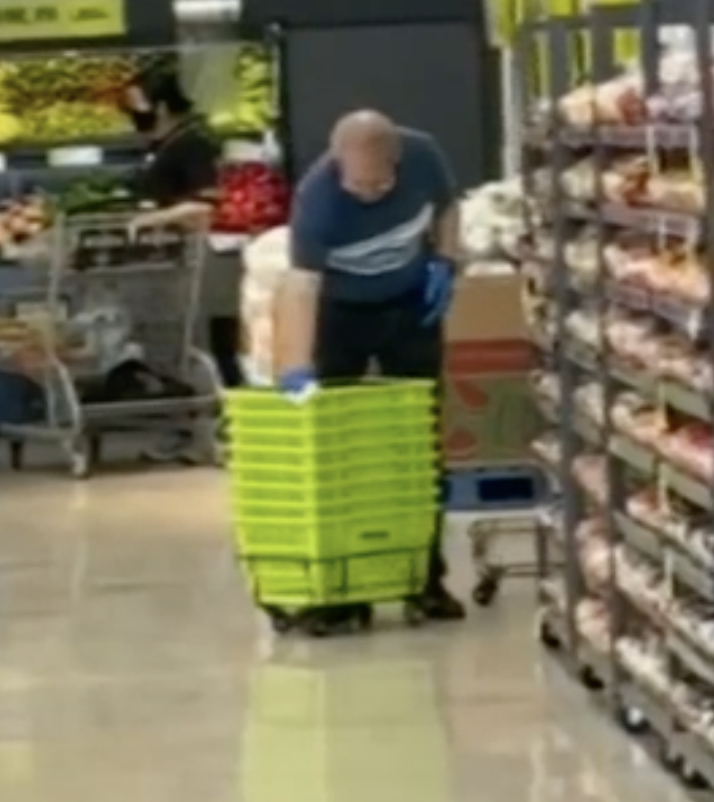 Photo shows supermarket cleaner wiping baskets with a cloth covered in his own saliva.