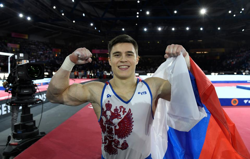 Russia's Nikita Nagornyy celebrates with his national flag after winning the men's all-around final at the FIG Artistic Gymnastics World Championships at the Hanns-Martin-Schleyer-Halle in Stuttgart, southern Germany, on October 11, 2019. (Photo by Thomas KIENZLE / AFP) (Photo by THOMAS KIENZLE/AFP via Getty Images)