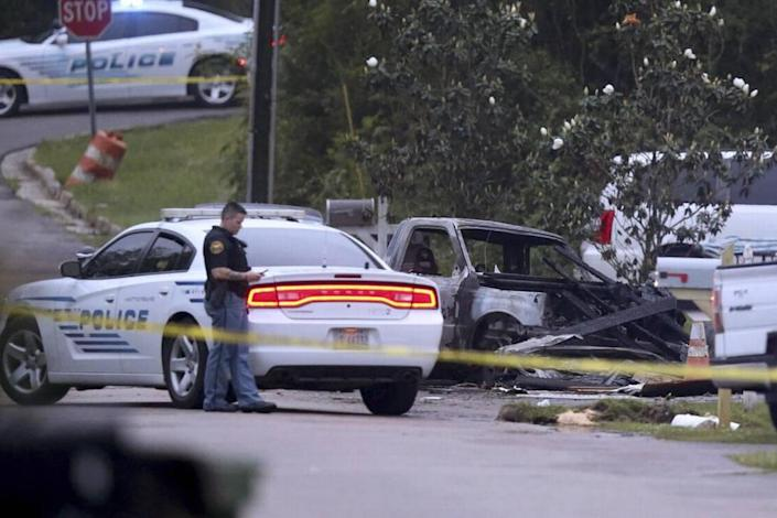 Hattiesburg police surround a burned automobile and a damaged home after a small plane crashed late Tuesday night in Hattiesburg, Miss., Wednesday May 5, 2021. Emergency officials in Mississippi say four people were killed.