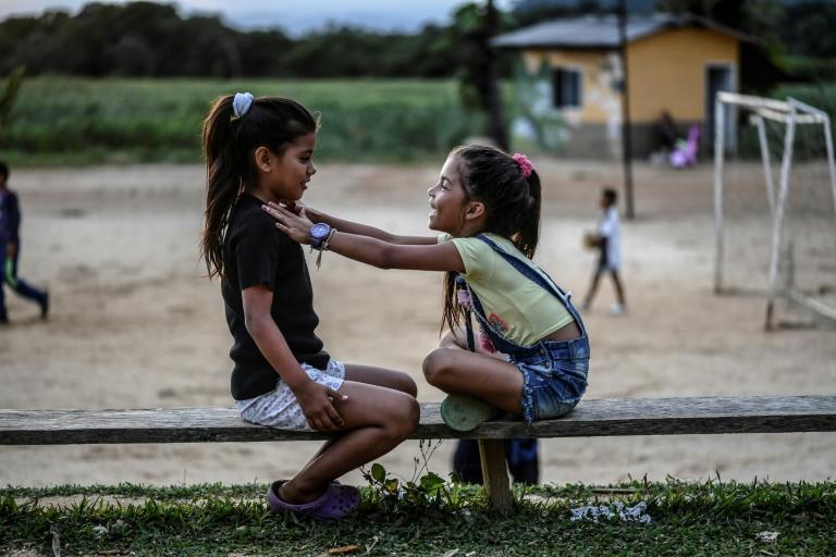 Two girls, the daughters of former FARC rebels, play in the municipality of La Montanita (AFP Photo/Juan BARRETO)
