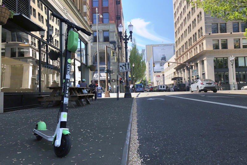 A Lime e-scooter sits parked on a street in downtown Portland, Ore., Thursday, May 9, 2019. A disability rights nonprofit group in Oregon filed a letter of complaint Thursday with the city of Portland over new rules about an electric scooter pilot program. (AP Photo/Gillian Flaccus)