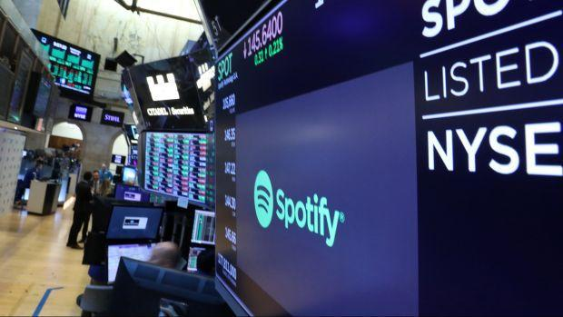 A screen displays the company logo and trading info for Spotify on the floor at the NYSE in New York