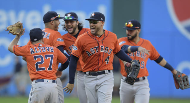 Houston Astros' George Springer (4) and teammates celebrate after defeating the Cleveland Indians in Game 3 of a baseball American League Division Series, Monday, Oct. 8, 2018, in Cleveland. (AP Photo/David Dermer)