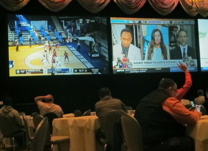 Customers watch a game in the NCAA basketball March Madness tournament on Friday March 19, 2021 at the Borgata casino in Atlantic City NJ. Last year, it was March sadness as the NCAA college basketball tournament got canceled days before it was supposed to start, due to the coronavirus. (AP Photo/Wayne Parry)