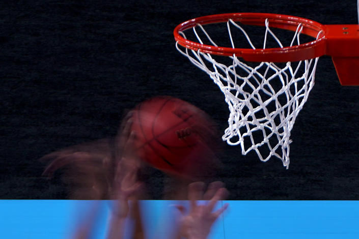 In this photo taken with a slow shutter, players compete for a rebound during the first half of a college basketball game between UConn and Syracuse in the second round of the women's NCAA tournament at the Alamodome in San Antonio, Tuesday, March 23, 2021. (AP Photo/Charlie Riedel)