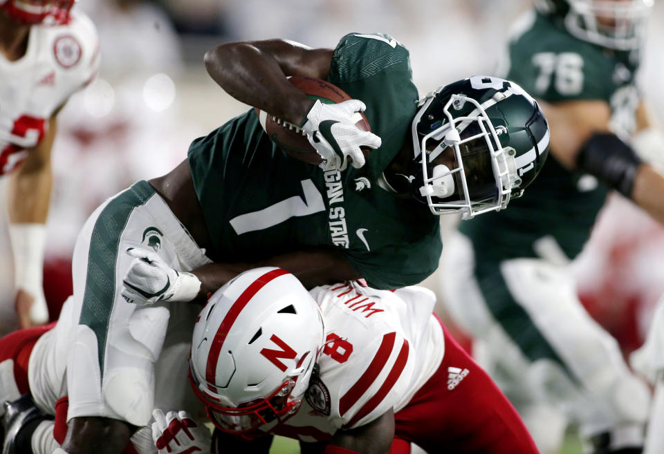 Michigan State's Jayden Reed, top, is stopped by Nebraska's Deontai Williams (8) during the first quarter of an NCAA college football game, Saturday, Sept. 25, 2021, in East Lansing, Mich. (AP Photo/Al Goldis)