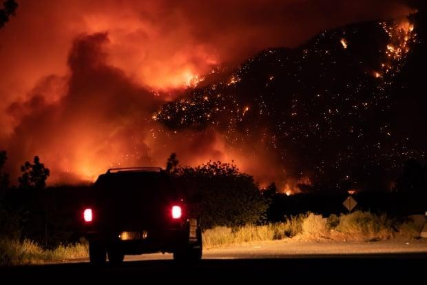 A motorist watches from a pullout on the Trans-Canada Highway as a wildfire burns on the side of a mountain in Lytton, B.C.. Emergency officials say people should set aside essential items in case they need to leave at a moment's notice. (Darryl Dyck/The Canadian Press - image credit)
