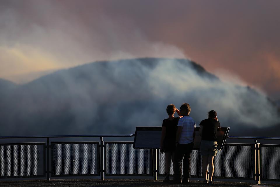 People watch as smoke from the Green Wattle Creek fire is seen from Echo Point lookout in Katoomba.