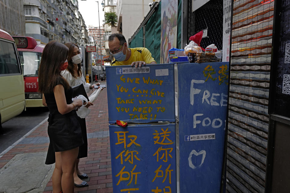 Two women chat with Ahmed Khan, center, yellow shirt, after putting foods inside a refrigerator at Woosung Street in Hong Kong's old-school neighborhood of Jordan Wednesday, Nov. 18, 2020. Khan, founder of a sports foundation on the same street, said he was inspired to create a community refrigerator after seeing a film about others doing the same thing. He found the refrigerator at a nearby refuse collection point and painted it blue. (AP Photo/Vincent Yu)