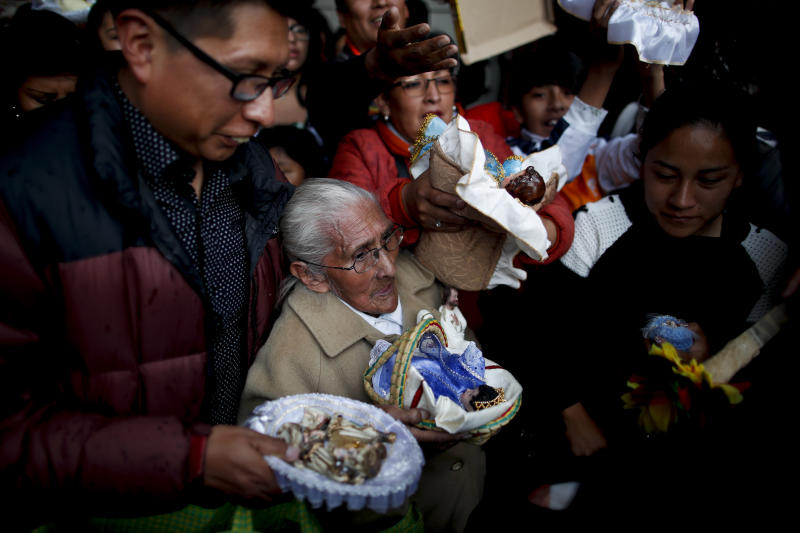 In this picture taken Monday, Jan. 6, 2020, people wait their turn to have their baby Jesus dolls blessed by a priest as they leave the Three Kings Day Mass at San Francisco Church in La Paz, Bolivia. Outside the church, many parishioners went to indigenous guides to get additional blessings that come from the country's belief in the Pachamama, or mother earth deity. (AP Photo/Natacha Pisarenko)