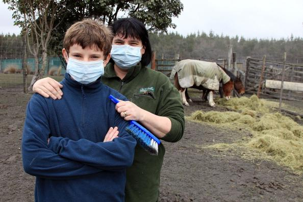 Josh Martin, 14, and mother Karen Martin pose while cleaning up a friends' property after Mt Tongariro erupted for the first time in over 100 years on August 7, 2012 in Tongariro National Park, New Zealand. Mt Tongariro erupted intermittently from 1855 to 1897. Although not an immediate threat to the community, the latest eruption may be the beginning of weeks, months or even years of volcanic activity. (Photo by Hagen Hopkins/Getty Images)