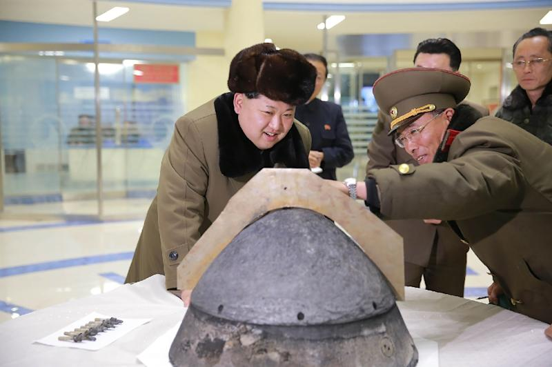 North Korean leader Kim Jong-Un (L) being briefed during an atmospheric re-entry environment simulation of a locally manufactured heat-resistant section of a ballistic missile warhead part at an undisclosed location in North Korea on March 15, 2016 (AFP Photo/KNS)