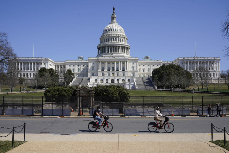 Bicyclists ride past an inner perimeter of security fencing on Capitol Hill in Washington, Sunday, March 21, 2021, after portions of an outer perimeter of fencing were removed overnight to allow public access. (AP Photo/Patrick Semansky)