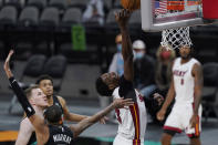 Miami Heat center Bam Adebayo (13) drives to the basket past San Antonio Spurs guard Dejounte Murray during the second half of an NBA basketball game in San Antonio, Wednesday, April 21, 2021. (AP Photo/Eric Gay)