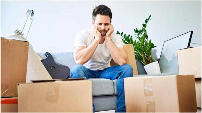 Man sits with boxes all around him