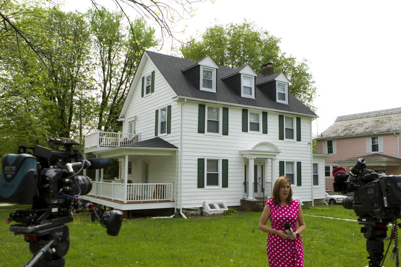 TV crews report form outside the house of Baltimore Mayor Catherine Pugh in Baltimore, MD., Thursday, April 25, 2019. Agents with the FBI and IRS are gathering evidence inside the two homes of Pugh and also in City Hall. (AP Photo/Jose Luis Magana)