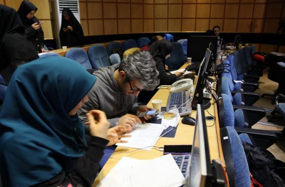 Press members follow the election results as vote counting for the 11th parliamentary elections continue in Tehran (Getty)