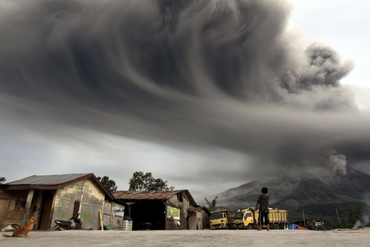 RNPS - PICTURES OF THE YEAR 2013 - A woman looks on as Mount Sinabung spews ash, as pictured from Sibintun village in Karo district, Indonesia's north Sumatra province November 18, 2013. Mount Sinabung continued to spew volcanic ash throwing a plume 8,000 meters into the atmosphere as thousands of residents remained in temporary shelters fearful of more eruptions, according to local media. REUTERS/Roni Bintang (INDONESIA - Tags: DISASTER ENVIRONMENT TPX)
