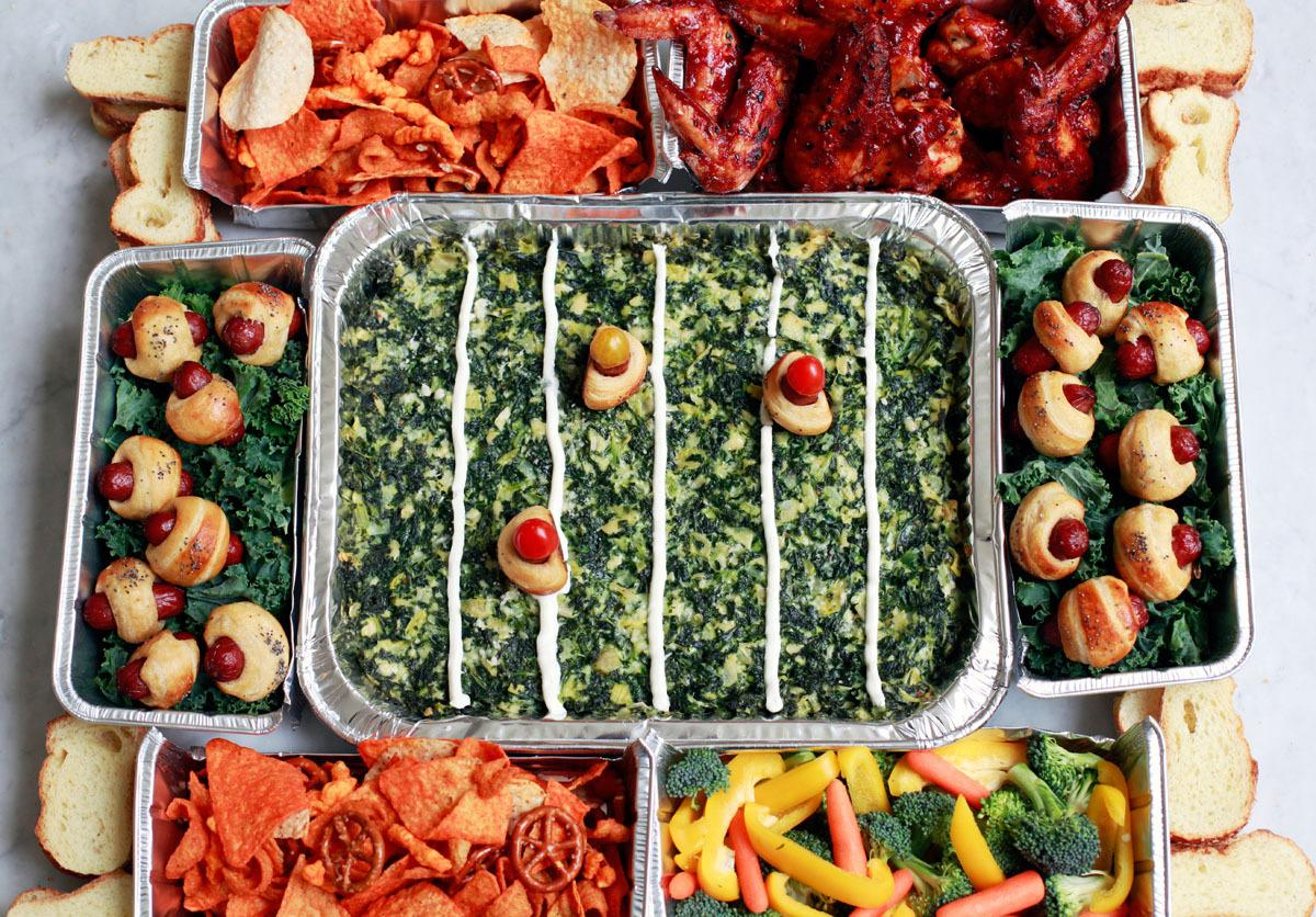 <p>Football season calls for going all out. This indulgent food stadium is packed full of your favorite game-day foods: heaping piles of pigs in a blanket, spicy chicken wings, and creamy artichoke-kale dip.<br /></p>