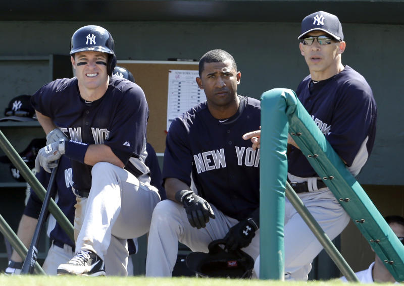 New York Yankees manager Joe Girardi, right, watches from the dugout along side Eduardo Nunez, center, and Jayson Nix during the second inning of an exhibition spring training baseball game against the Miami Marlins Friday, March 8, 2013, in Jupiter, Fla. The Marlins won 6-1. (AP Photo/Jeff Roberson)