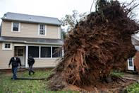 Men survey a large tree that fell during Hurricane Sandy on October 30, 2012 in Washington, DC. The storm has claimed at least 16 lives in the United States, and has caused massive flooding across much of the Atlantic seaboard. US President Barack Obama has declared the situation a 'major disaster' for large areas of the US East Coast including New York City, with wide spread power outages and significant flooding in parts of the city. (Photo by Brendan Hoffman/Getty Images)