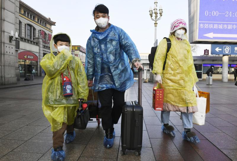 Passengers wear masks and raincoats at Beijing Station on Feb. 10, 2020, amid the spread of the new coronavirus. Source: AAP