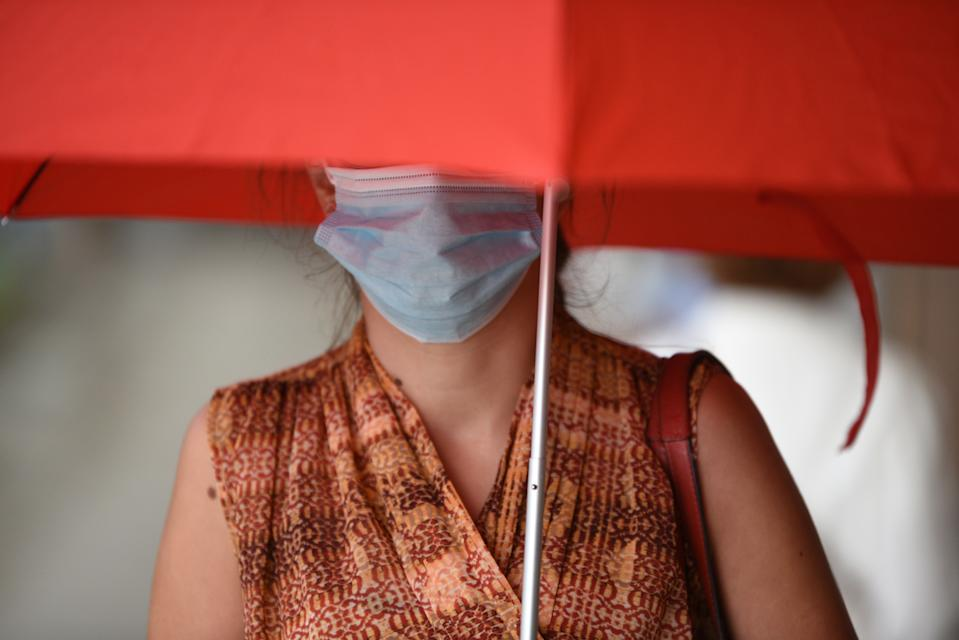 A woman carrying an umbrella as protection from the rain is seen wearing a facemask as a preventive measure against the spread of coronavirus. (Photo by Jorge Sanz / SOPA Images/Sipa USA)