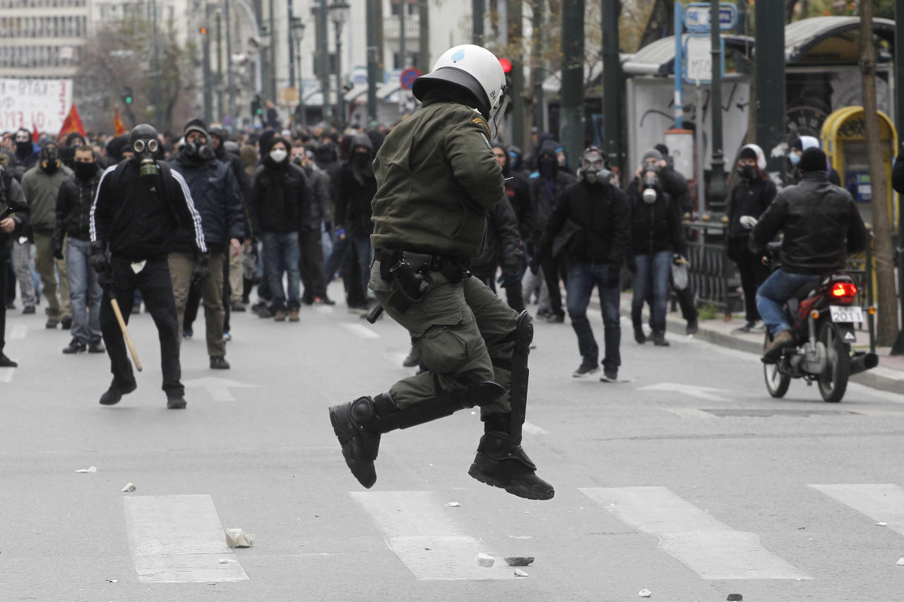 A riot policeman tries to avoid a stone thrown by a protester during clashes in Athens, Friday, Feb. 10, 2012. Thousands took to the streets of Athens as unions launched a two-day general strike against planned austerity measures on Friday, a day after Greece's crucial international bailout was put in limbo by its partners in the 17-nation eurozone. (AP Photo/Petros Giannakouris)