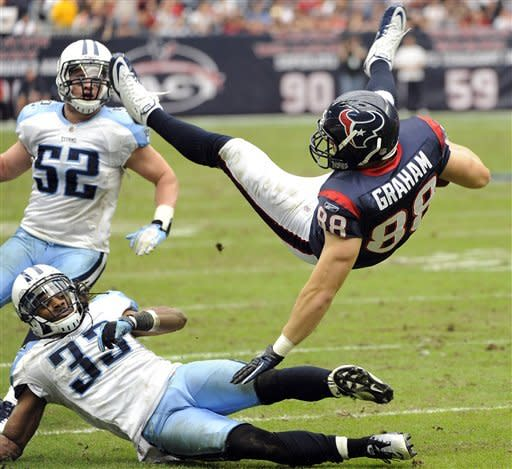 Houston Texans tight end Garrett Graham (88) is upended by Tennessee Titans free safety Michael Griffin (33) as Titans' Colin McCarthy (52) watches in the third quarter of an NFL football game on Sunday, Jan. 1, 2012, in Houston. The Titans won 23-22. (AP Photo/Dave Einsel)