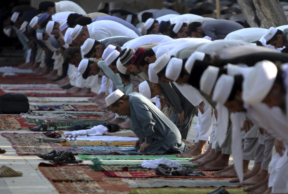 Muslims offer Eid al-Fitr prayer in an open area in Peshawar, Pakistan, Sunday, May 24, 2020. Millions of Muslims across the world are marking a muted and gloomy holiday of Eid al-Fitr, the end of the fasting month of Ramadan _a usually joyous three-day celebration that has been significantly toned down as coronavirus cases soar. (AP Photo/Muhammad Sajjad)
