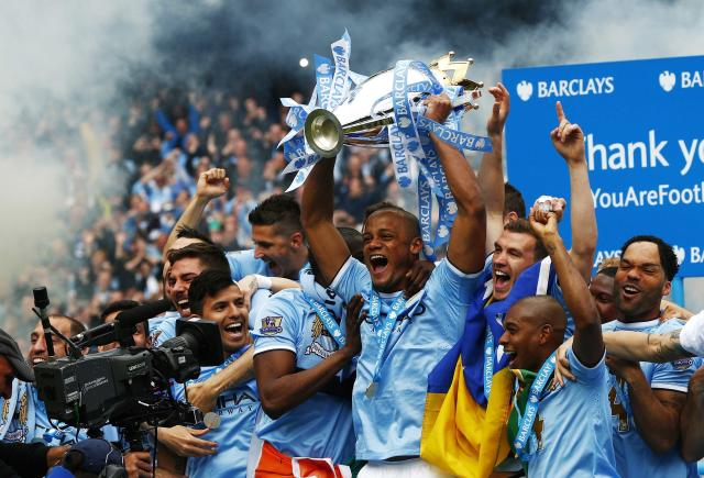 """Manchester City's captain Vincent Kompany (C) celebrates with the English Premier League trophy following their soccer match against West Ham United at the Etihad Stadium in Manchester, northern England May 11, 2014. REUTERS/Darren Staples (BRITAIN - Tags: SPORT SOCCER TPX IMAGES OF THE DAY) FOR EDITORIAL USE ONLY. NOT FOR SALE FOR MARKETING OR ADVERTISING CAMPAIGNS. NO USE WITH UNAUTHORIZED AUDIO, VIDEO, DATA, FIXTURE LISTS, CLUB/LEAGUE LOGOS OR """"LIVE"""" SERVICES. ONLINE IN-MATCH USE LIMITED TO 45 IMAGES, NO VIDEO EMULATION. NO USE IN BETTING, GAMES OR SINGLE CLUB/LEAGUE/PLAYER PUBLICATIONS"""