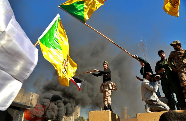 Protesters wave militia flags in front of the U.S. Embassy compound in Baghdad on Tuesday. (Photo: Khalid Mohammed/AP)