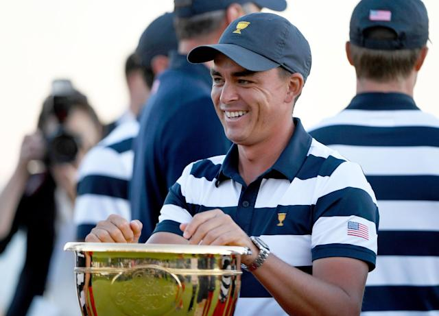 """<div class=""""caption""""> <a class=""""link rapid-noclick-resp"""" href=""""/pga/players/9633/"""" data-ylk=""""slk:Rickie Fowler"""">Rickie Fowler</a> smiles while looking at the trophy after the U.S. Team defeated the International Team 19 to 11. </div> <cite class=""""credit"""">Chris Condon/PGA Tour</cite>"""