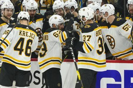 May 16, 2019; Raleigh, NC, USA; Boston Bruins left wing Brad Marchand (63) celebrates with center Patrice Bergeron (37) after scoring a third period empty net goal against the Carolina Hurricanes in game four of the Eastern Conference Final of the 2019 Stanley Cup Playoffs at PNC Arena. The Boston Bruins defeated the Carolina Hurricanes 4-0. Mandatory Credit: James Guillory-USA TODAY Sports