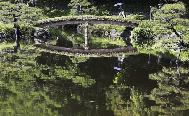 <p>A woman with a parasol crosses a bridge on the pond at Kiyosumi Gardens in Tokyo, May 19, 2017. The temperature in Tokyo soared to 26.3 degrees Celsius (79 degrees Fahrenheit). (Photo: Koji Sasahara/AP) </p>