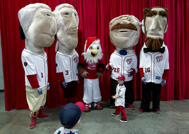 The Presidential character mascots of the Washington Nationals baseball team, from left, Thomas Jefferson, George Washington, Teddy Roosevelt and Abraham Lincoln take pictures with children during the Winter Fest celebration with fans at Washington Convention Center in Washington, Saturday, Dec. 16, 2017. ( AP Photo/Jose Luis Magana)