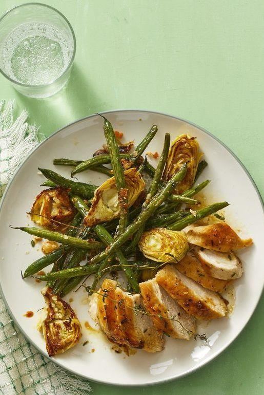 """<p>This gluten-free dish is full of tasty and good-for-you ingredients, like green beans and artichoke hearts roasted with Parmesan and thyme. </p><p><em><a href=""""https://www.womansday.com/food-recipes/a32303951/lemon-thyme-chicken-recipe/"""" rel=""""nofollow noopener"""" target=""""_blank"""" data-ylk=""""slk:Get the Lemon-Thyme Chicken recipe."""" class=""""link rapid-noclick-resp"""">Get the Lemon-Thyme Chicken recipe.</a></em></p>"""