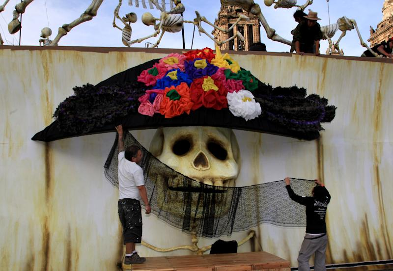 "Artists decorate a traditional Mexican ""Catrina"" as part of the Day of the Dead celebrations in Mexico City's Zocalo, Wednesday, Oct. 30, 2013. Mexicans celebrate Day of the Dead to honor deceased loved ones, a tradition that coincides with All Saints Day and All Souls Day on Nov. 1 and 2. (AP Photo/Marco Ugarte)"