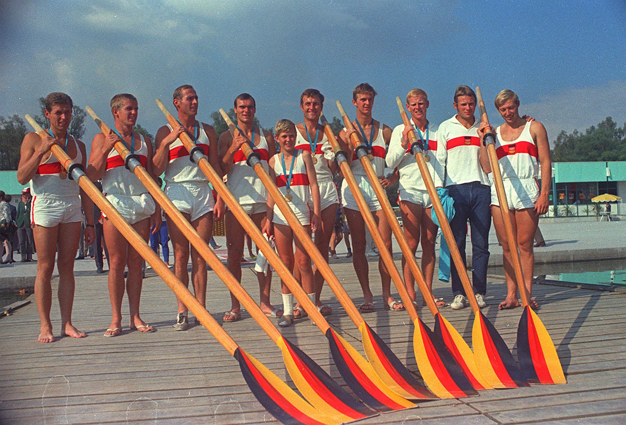 Los ocho miembros del equipo de Alemania Occidental en la competencia final de remo, junto a su entrenador...