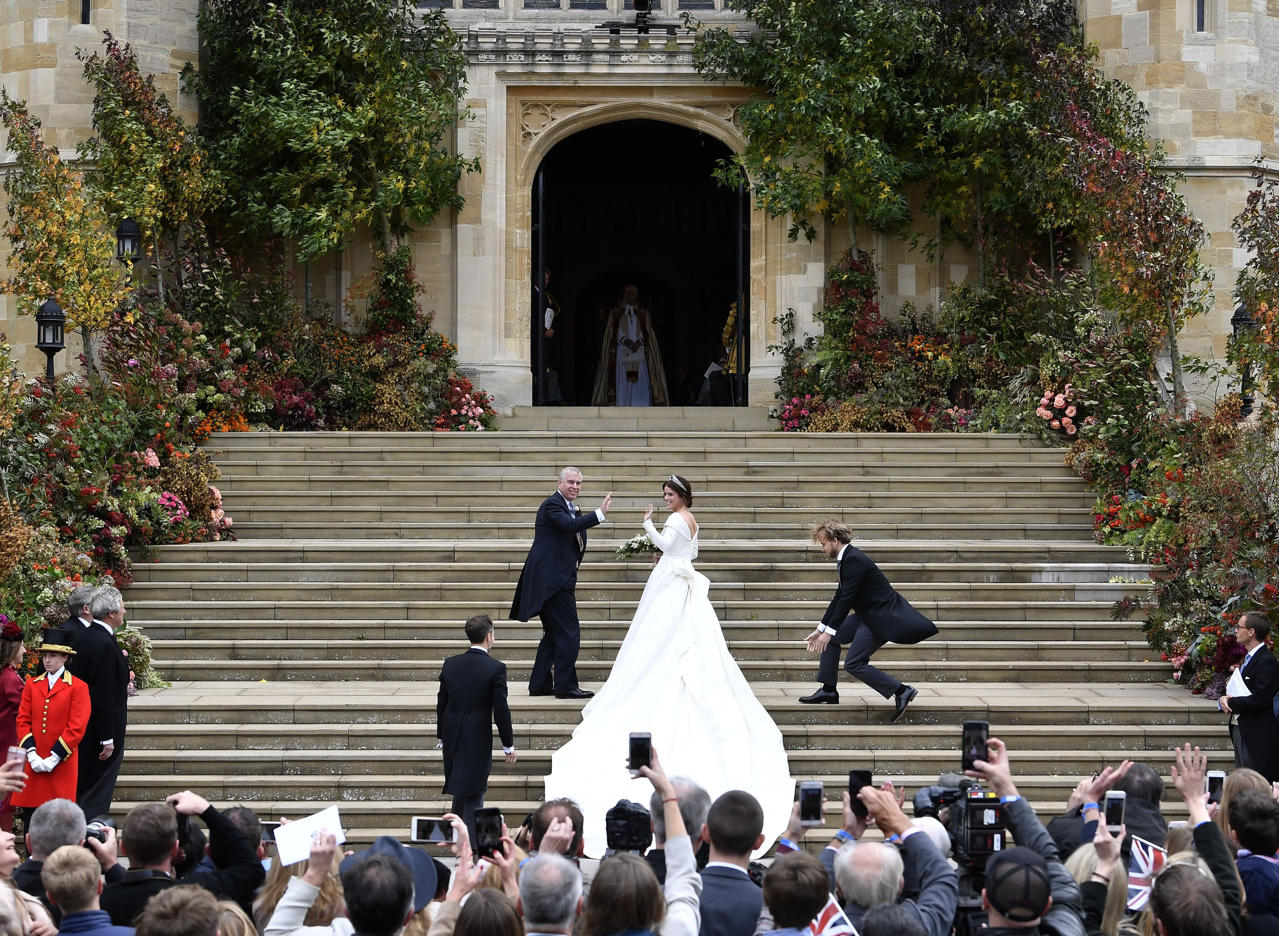 Britain's Princess Eugenie, accompanied by her father Prince Andrew, arrives for her wedding ceremony...