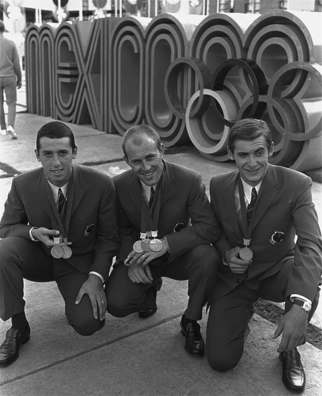 Tres miembros del equipo de ciclismo francés posan el 21 de octubre de 1968, frente al emblema de la...