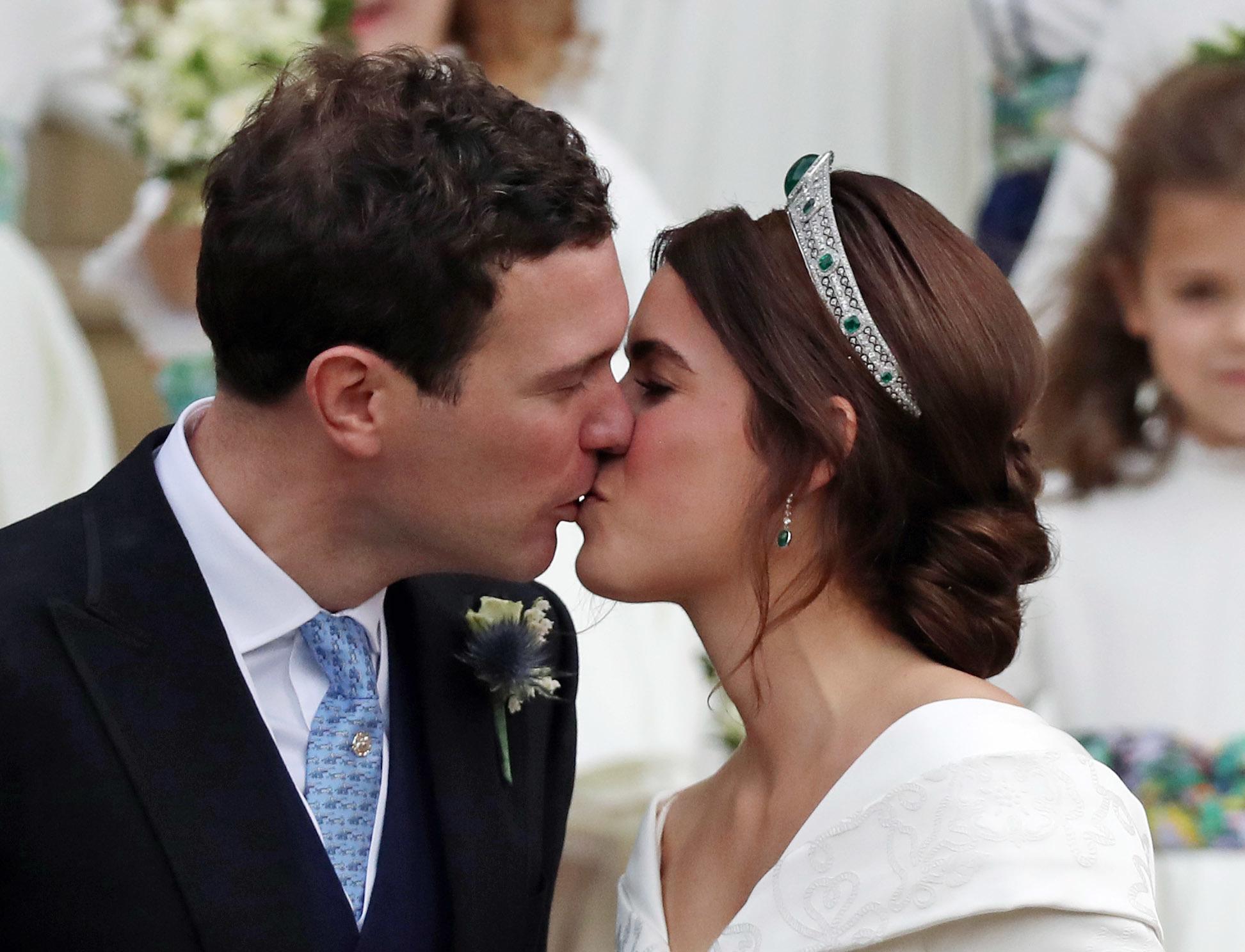 WINDSOR, ENGLAND - OCTOBER 12: Princess Eugenie of York and her husband Jack Brooksbank kiss on the steps...