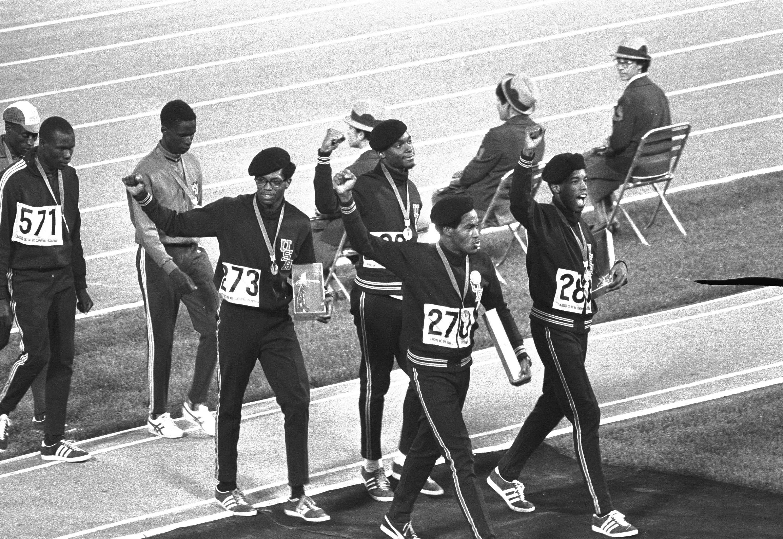 Cuatro miembros negros del equipo de relevo 4x400 metros de Estados Unidos su salida de la premiación,...